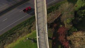 Vrouw die op een brug over een snelweg hierboven lopen van stock footage