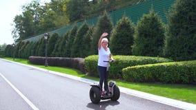 Vrouw die op een Elektrische Persoonlijke Vervoerder op een stille straat berijden stock videobeelden