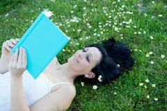 Vrouw die op een gebloeide weide liggen die een boek lezen royalty-vrije stock afbeeldingen