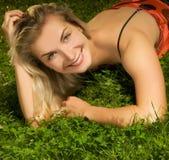 Vrouw die op een groen gras ligt Royalty-vrije Stock Foto's