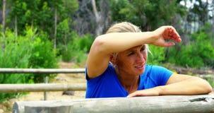Vrouw die op een hindernis tijdens hinderniscursus 4k leunen stock footage