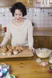 Vrouw die op een houten lijst een dienblad met cupcakes zetten en gebakken des Stock Foto