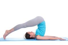 Vrouw die op een mat ligt die yoga doet Royalty-vrije Stock Foto's