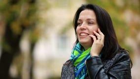 Vrouw die op een mobilecelltelefoon bij park dicht omhoog spreken stock video