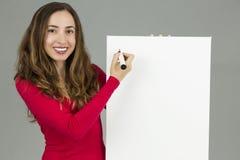Vrouw die op een op de markt brengende raad met een teller schrijven Stock Foto's