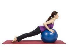 Vrouw die op een pilatesbal uitwerken Stock Foto