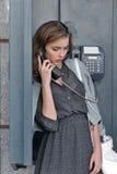 Vrouw die op een publieke telefooncel op de straat spreken royalty-vrije stock afbeelding