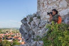 Vrouw die op een rotsachtig vooruitzicht fotograferen stock fotografie
