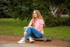 Vrouw die op een skateboard zit Stock Fotografie