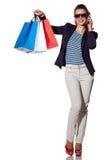 Vrouw die op een smartphone spreken en het winkelen zakken tonen Royalty-vrije Stock Foto's