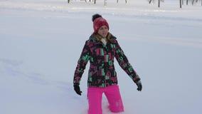 Vrouw die op een sneeuwbank in de winter op het gebied van vermoeide dalingen op de sneeuw lopen stock video