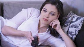 Vrouw die op een Sofa Watching-TV liggen stock videobeelden