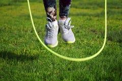 vrouw die op een touwtjespringen in park springen Stock Afbeeldingen