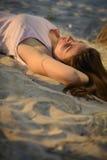 Vrouw die op een zandstrand bepaalt op zonsondergang Stock Foto