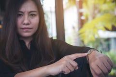 Vrouw die op een zwart polshorloge op haar wapen richten stock afbeeldingen
