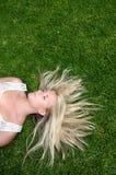 Vrouw die op gazon rust stock foto