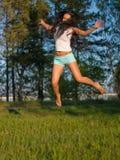 Vrouw die op gebied springt Stock Afbeelding