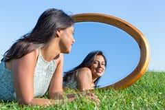 Vrouw die op gras buiten het kijken in spiegel liggen royalty-vrije stock foto's