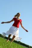 Vrouw die op gras danst Royalty-vrije Stock Afbeeldingen