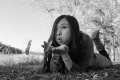 Vrouw die op gras leggen Stock Afbeeldingen