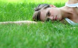 Vrouw die op gras liggen stock foto