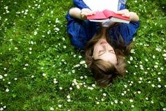 Vrouw die op gras met boek ligt royalty-vrije stock afbeeldingen