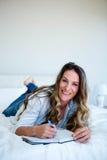 vrouw die op haar bed die in een boek liggen schrijven stock foto's