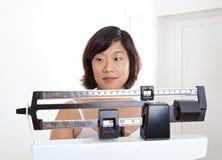 Vrouw die op Haar Gewicht op de Schaal van het Gewicht let Royalty-vrije Stock Afbeelding