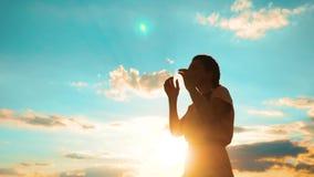 vrouw die op haar knieën bidden het meisje vouwde haar indient gebedsilhouet bij levensstijlzonsondergang langzame geanimeerde vi stock video