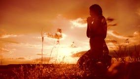 vrouw die op haar knieën bidden het meisje vouwde haar indient gebedsilhouet bij zonsondergang langzame geanimeerde video Het mei stock video