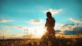 vrouw die op haar knieën bidden het meisje vouwde haar indient gebedsilhouet bij zonsondergang langzame geanimeerde video Het mei stock videobeelden