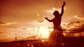 vrouw die op haar knieën bidden het meisje vouwde haar indient gebedsilhouet bij zonsondergang langzame geanimeerde video levenss stock videobeelden