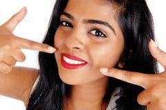 Vrouw die op haar witte tanden richten stock fotografie