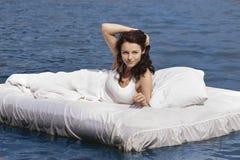 Vrouw die op het bed in het overzees ligt Royalty-vrije Stock Foto