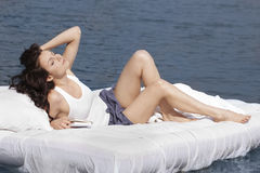 Vrouw die op het bed in het overzees ligt Stock Afbeeldingen