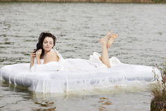 Vrouw die op het bed in het overzees ligt Stock Foto's