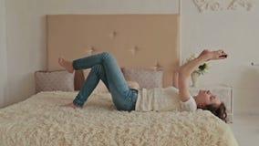 Vrouw die op het bed liggen die haar cellphone gebruiken stock videobeelden
