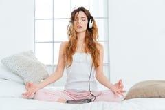 Vrouw die op het bed mediteren Stock Foto's