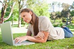 Vrouw die op het gazon met haar laptop ligt Royalty-vrije Stock Fotografie