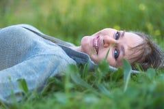 Vrouw die op het gras in aard leggen Royalty-vrije Stock Fotografie