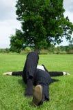 Vrouw die op het gras met boom in de achtergrond liggen royalty-vrije stock foto's