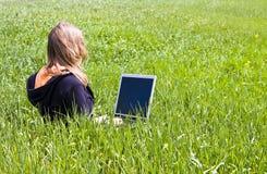 Vrouw die op het gras wordt verbonden royalty-vrije stock afbeeldingen