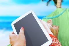 Vrouw die op het overzees met een witte tablet rusten Stock Afbeelding