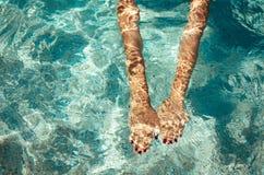 Vrouw die op het overzees zwemmen Vrouwelijke handen onder duidelijk zeewater Stock Afbeelding