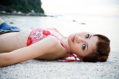 Vrouw die op het strand liggen stock afbeeldingen