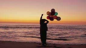 Vrouw die op het strand met ballons lopen stock videobeelden