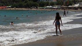 Vrouw die op het strand met mensen en golven lopen stock footage