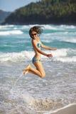 Vrouw die op het strand springen Stock Afbeeldingen