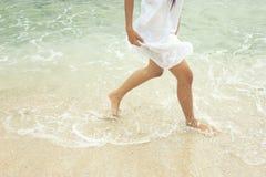 Vrouw die op het zandige strand lopen - Selectieve nadruk Stock Afbeelding