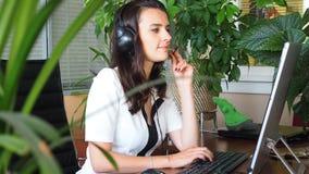 Vrouw die op hoofdtelefoon in bureau met cliënt spreken die door installaties wordt omringd stock videobeelden